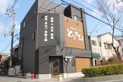 シックな黒の外壁と木の格子が印象的な居酒屋さんのサイン